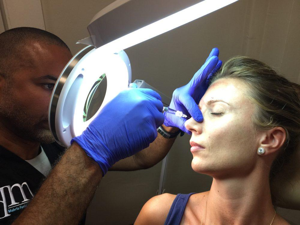Dr. Mabrie performing nonsurgical rhinoplasty procedure on patient