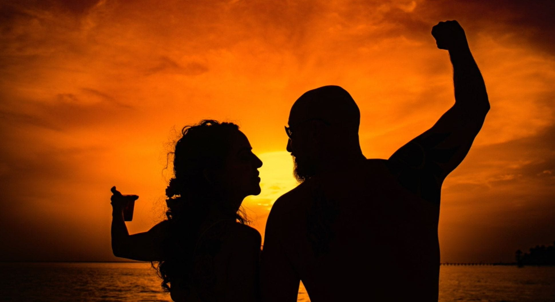 Michelle and her husband toasting sunset on the beach